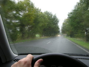 hand on steering wheel background is rainy road with trees on both sides