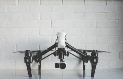 white drone against white brick wall